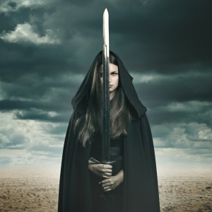 Beautiful dark woman with sword in a desert and stormy landscape. Fantasy and surreal