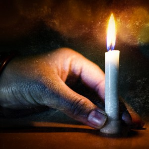 hand holding candle in the dark night indoor on bokeh textured grungy background